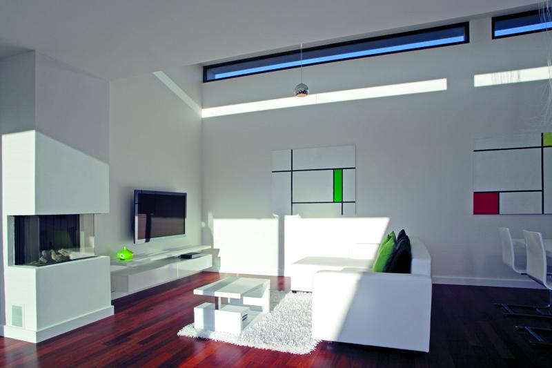 Minimalistický interiér otevřeného denního prostoru dokonale ladí s obrazy na stěnách. S bílými stěnami a nábytkem kontrastuje podlaha ze dřeva merbau, která celý dům pocitově prohřála.