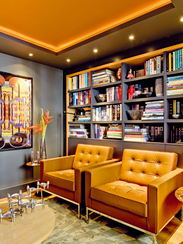 Prostor bývalé kuchyně slouží nyní jako čítárna. Uhlově šedá barva na stěnách a efektní nasvícení vytvářejí klidnou, tlumenou atmosféru. FOTO: MATT CHUNG