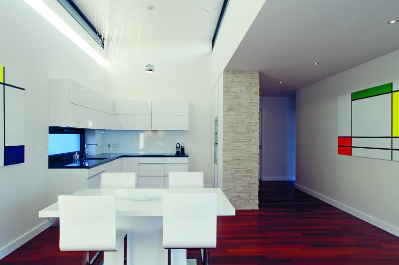 Oživením čisté architektury domu je světlo – přes úzká okna ve zvýšené části otevřeného prostoru vytváří na stěnách proměnlivé světelné efekty a vyjímá denní prostor z hranic standardu. Úzká okna ve zvýšené části místnosti přinášejí do prostoru zvláštní světlo.