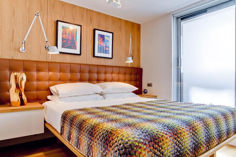 Ložnice barevně a materiálově koresponduje sčítárnou – čelo postele nechali očalounit stejně jako křesla o patro níže. FOTO: MATT CHUNG