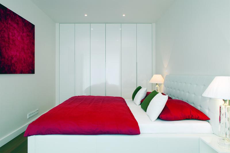 Ve stejném stylu je zařízen celý dům – kontrast jasných barev na bílém pozadí pokračuje duchem Mondrianových obrazů i v ložnici. Všechny skříně v domě jsou nenápadně vestavěny do nik ve stěnách.