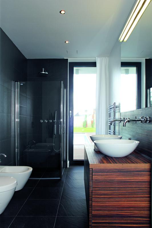 Působivá kombinace obkladu a dlažby v barvě břidlice, elegantní bílé keramiky a dřeva wenge je záměrně stejná v obou koupelnách v domě. Exotické dřevo místnosti dodává pocit tepla a kontrastní bílá stěna oživuje.