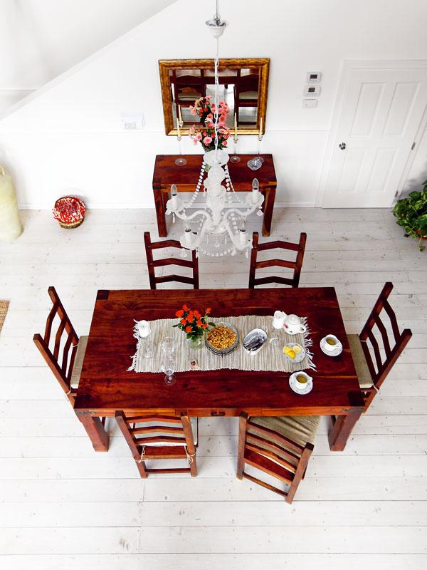 Vcentru domu, vjeho části otevřené až po hřeben krovu, je jídelna svelkým dřevěným stolem – takovým, u kterého rády zakotví všechny návštěvy. I když vypadá být šitý na míru velkému prostoru, tento nábytek si do nové jídelny přinesli ze starého bytu. FOTO: Dano Veselský