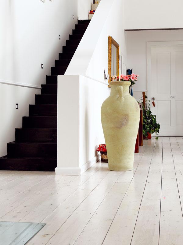 Dva základní požadavky na schodiště byly, aby zabralo co nejméně místa aaby nebylo zbytečně drahé. Jednoduché přímé schody vanglickém stylu, vyrobené ze smrkového dřeva, splnily oba, navíc se pod ně skryla i komora – jediný větší odkládací prostor v domě. FOTO: Dano Veselský