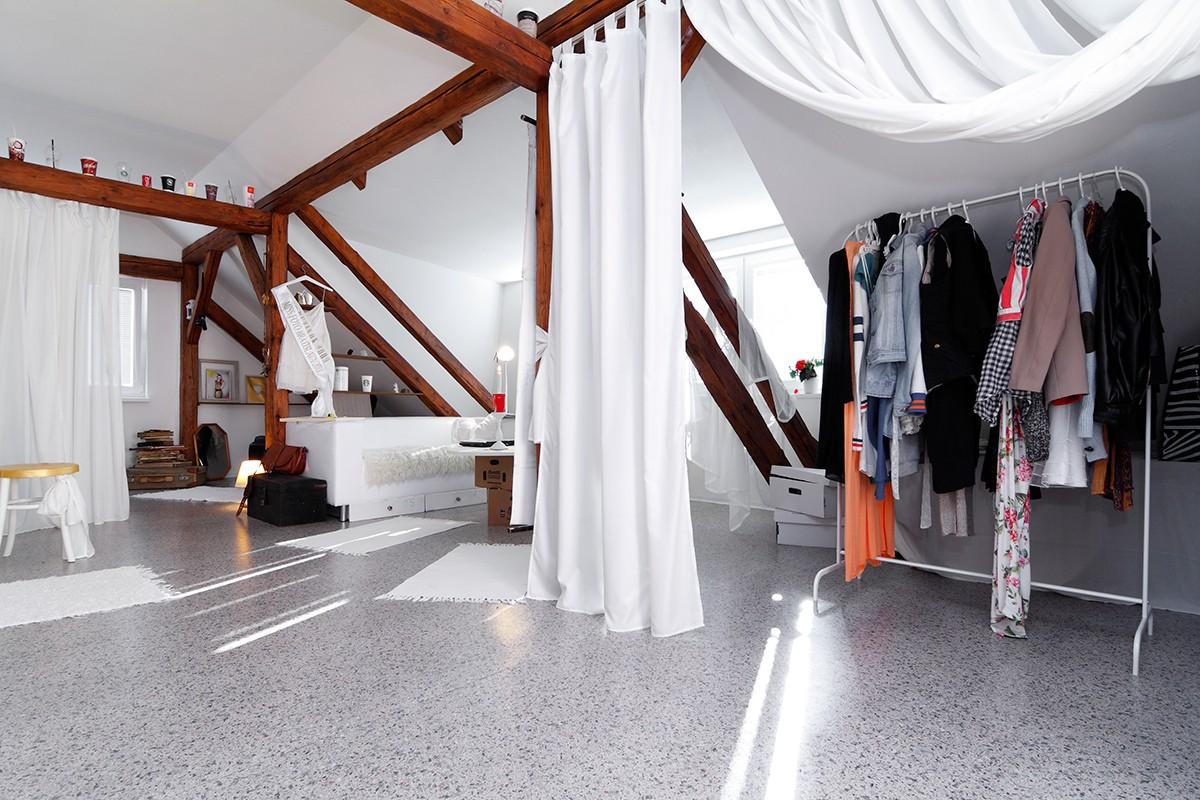 Závěsy domácí výroby využila Nikola k rozdělení velké místnosti, ale i k oddělení úložných prostorů. Všechny stěny jsou tu šikmé, takže se sem nedá umístit klasická velká skříň. FOTO: Dano Veselský