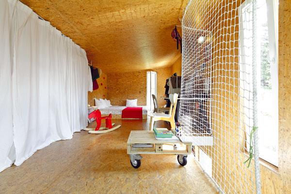 Dispoziční uspořádání malého prostoru vychází ze světelných poměrů, například postel je logicky v nejtmavším koutě. Prvky lezecké stěny nad matrací postele – vtipný nápad, který určitě ocení děti. FOTO: DANO VESELSKÝ