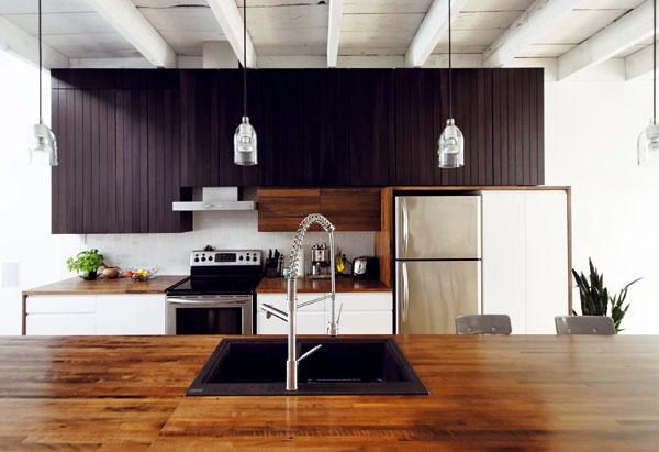Jednoduše řešená kuchyň je nejdůležitějším prostorem vdomě. Dřevěný ostrůvek se zapuštěným dřezem slouží i jako stůl pro posezení spřáteli, nebo pro rychlou snídani. foto Marc-Andre Plasse