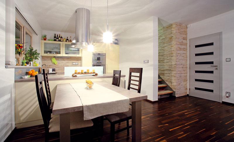 Kuchyňská linka ve vanilkové barvě je stejně jako všechen nábytek vdomě vyrobena na míru. Navazuje na ni jídelní sezení sprostorným stolem. Schodiště tvoří ocelová konstrukce. Nášlapy nahradí laminátové desky s dekorem broušeného plechu a jako podstupnice majitelé použijí kamenný obklad. FOTO: WWW.PROJEKTYDOMU.CZ