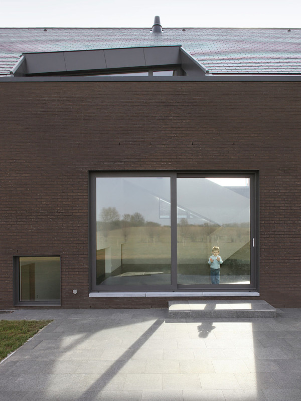 Velkoformátové okno na jižní straně fasády umožňuje obyvatelům neustálou komunikaci s venkovním prostředím. V zimě navíc zajišťuje maximální využití solárních zisků. Foto: Filip Dujardin