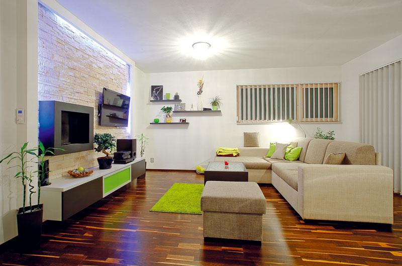 Prostor obývacího pokoje doplňuje sádrokartonová nika obložená kamenem. Majitelé do ní umístili televizor, nepřímé osvětlení a biokrb, který vytváří příjemnou atmosféru. Podlahu tvoří třívrstvé dřevěné parkety zafrického dubu abíleného jasanu. FOTO: WWW.PROJEKTYDOMU.CZ