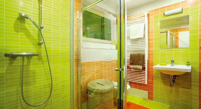 Do koupelny v přízemí si majitelé vybrali zasklený sprchový kout. Zelenou barvu, která je barvou podlaží, doplnili oranžovou. FOTO: WWW.PROJEKTYDOMU.CZ