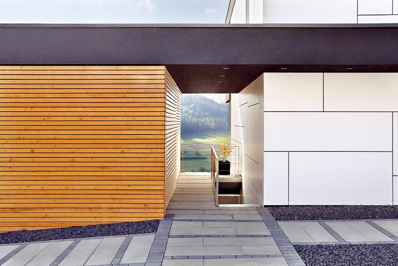 Mezi domem a garáží je možné sejít přímo na velkou jižní terasu domu. Modřínový obklad na garáži, který oživuje minimalisticky pojatý dům, pohladí po duši. Foto Daniel Stauch