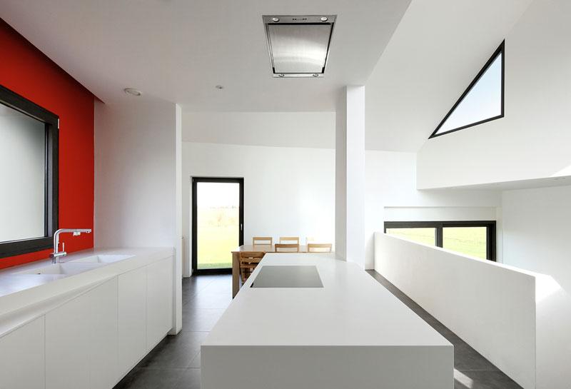 Červená stěna kuchyně je jedinou výraznou barvou v interiéru. Zbytek barevného divadla už rozehrávají jen sluneční paprsky a okolní krajina při pohledu ven. Foto: Filip Dujardin