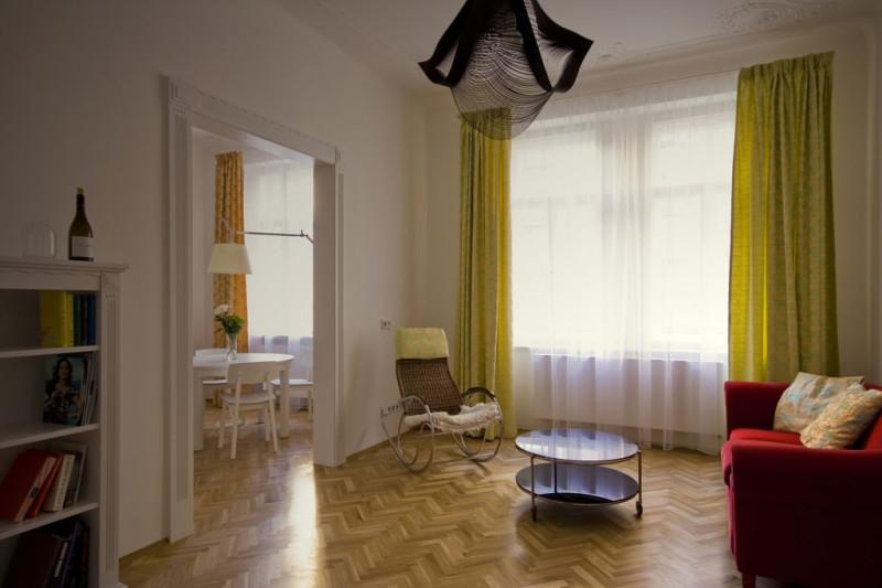 """Obývací pokoj je – stejně jako celý interiér – zařízen vzdušně a vyhýbá se """"přeplácanosti"""". Dlouhé závěsy a záclony podtrhují výšku stropů a prostornost celého bytu. Foto: Veronika Brůhová a Štěpán Zápotocký"""