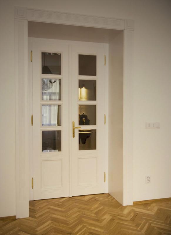 Kuchyň v bílém provedení odkazuje na dávný původ bytu historizujícími porcelánovými úchytkami, které tematicky navazují na porcelánové vypínače použité v předsíni. Foto: Veronika Brůhová a Štěpán Zápotocký