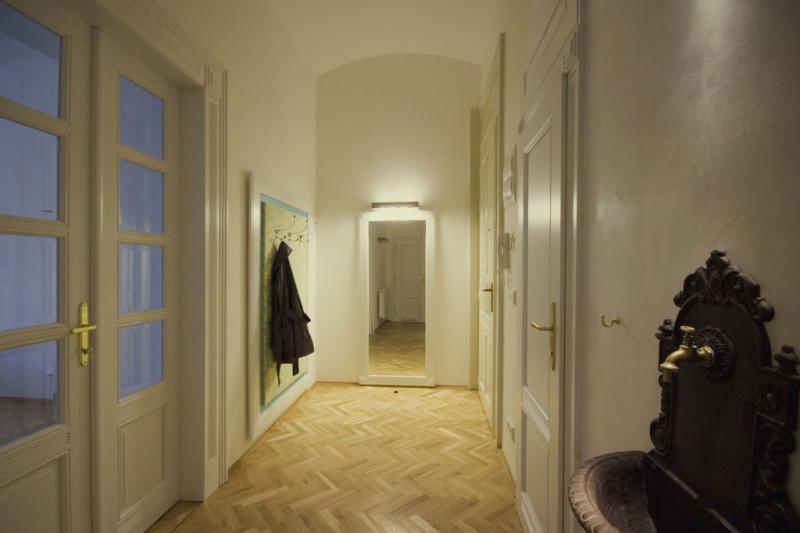 Do bytu se vstupuje skrze vstupní halu, přivítá vás tu věšáková stěna s dobovým dekorem v pastelových tónech. Stejný najdete i na dalších místech interiéru. Vstupní dveře, přestože působí historicky, jsou ve skutečnosti replikou se soudobými bezpečnostními prvky. Foto: Veronika Brůhová a Štěpán Zápotocký