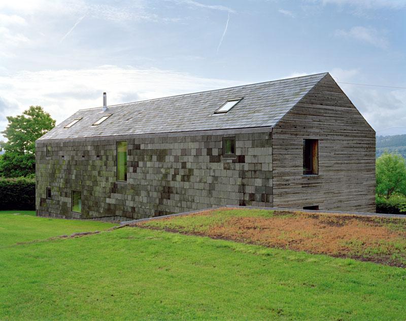 Dlouhý dům obdélného půdorysu zbřidlice a modřínu navazuje na tradiční typologii vesnického domu ve Walesu. Citlivá reinterpretace známých forem spolu snovými nápady a novými technologiemi je daleko autentičtější než bezduché kopírování. Foto Feilden Fowles