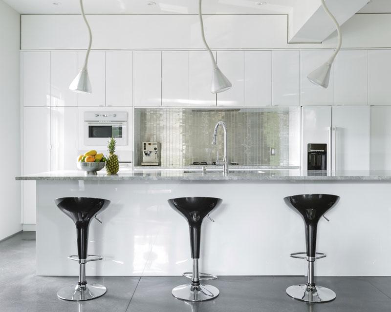 Jednotnou barvu kuchyňské linky − v odkazu na šedou desku pultu − ozvláštňuje nika se stříbrným obkladem.  Foto: Ulysse Lemerise Bouchard (YUL Photo)