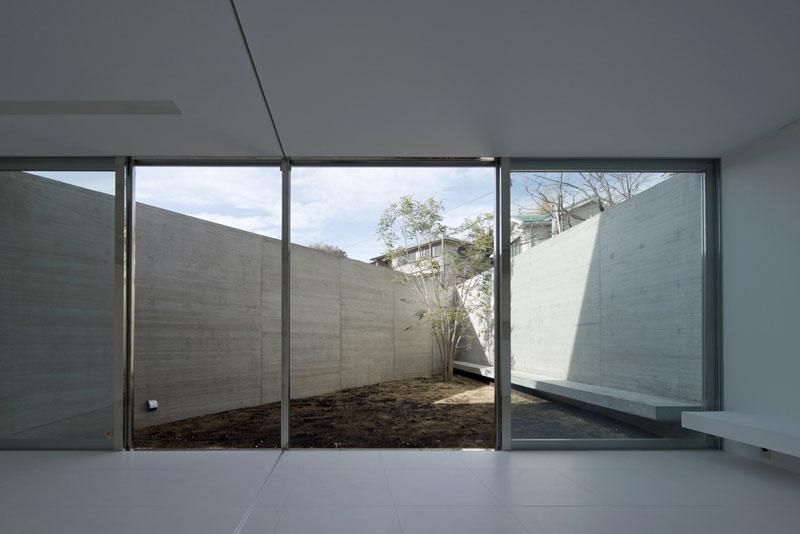 """V samé špičce trojúhelníku obvodové zdi, v níž se nachází nepříliš veliký dvorek, zasadili majitelé jakýsi """"památný"""" strom. Vedle duchovního významu ale nese i funkci ryze praktickou - do budoucna má zajistit obyvatelům také soukromí, protože okna protějšího domu jsou namířena přímo jejich směrem. Foto: Masao Nishikawa"""
