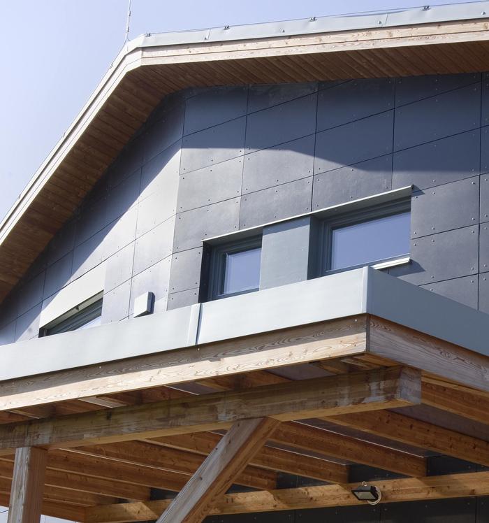 Na atiky plochých střech a oplechování zvolil architekt předzvětralý titanzinkový plech. Dřevěná okna jsou natřena v odstínu antracit.