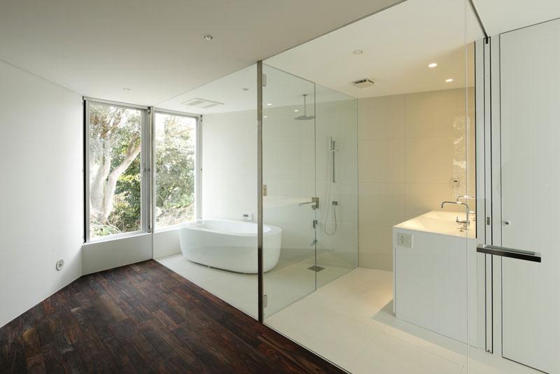 """V opačné části přízemí se nachází ložnice s přilehlou koupelnou, přepaženou jen skleněnou stěnou. Architekti se tu pokusili o malý experiment, jehož cílem bylo vnést do prostoru pomocí kontaktu s """"vypůjčenou krajinou"""" relaxační atmosféru hotelových resortů. Foto: Masao Nishikawa"""