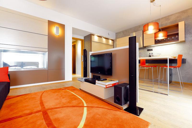 Oranžový koberec a další doplňky narušují dominující neutrální přírodní odstíny interiéru. FOTO DANO VESELSKÝ