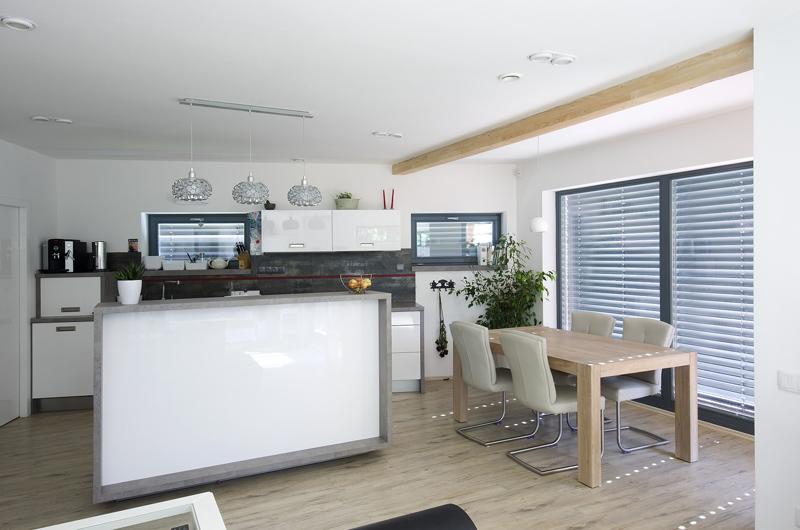 Kuchyně je zařízena v moderním minimalistickém stylu, jeho chlad zmírňují čalouněné židle, ozdobné osvětlení pracovní plochy a další interiérové doplňky.