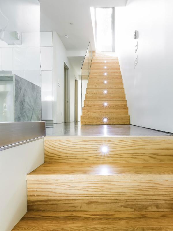 Dřevěný obklad jednotlivých schodů vyniká skrze lesklou plochu skleněné desky, která funguje jako zábradlí, a dodává interiéru hřejivé teplo domova. Foto: Ulysse Lemerise Bouchard (YUL Photo)