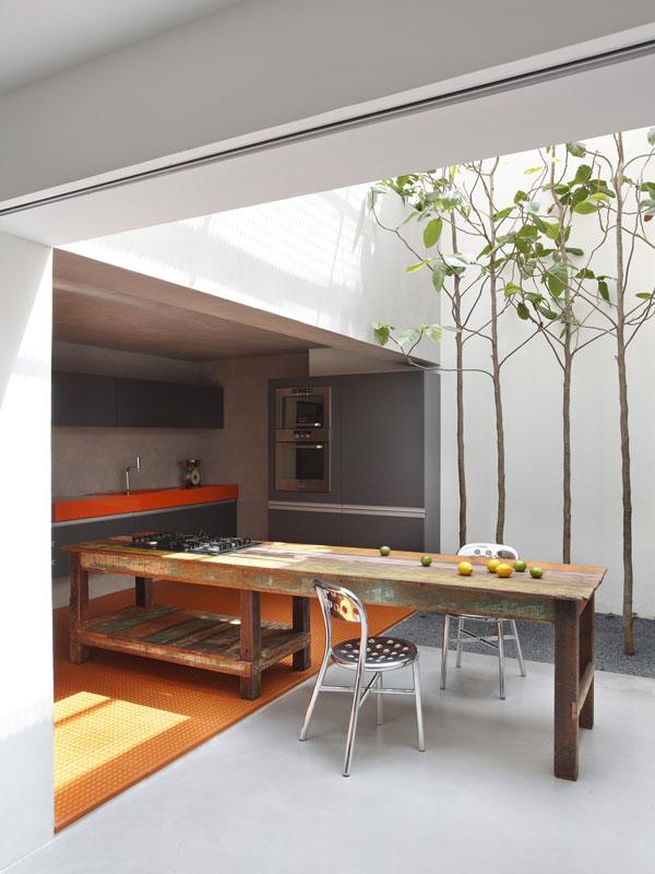 Vaření na čerstvém vzduchu. Na obývací pokoje prostupující do exteriéru jsme si už docela zvykli, ale kuchyňský stůl napůl uvnitř, napůl venku? A proč ne! Díky otvíravé skleněné střeše je možné vše. Foto: Denilson Machado – MCA Estúdio