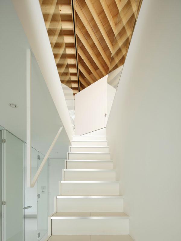 Bílá barva stěn, noblesní šeď pohledového betonu a čiré sklo jsou společným jmenovatelem všech prostor interiéru. Jednolitost a jednoduchost těchto ploch rozbíjí až složitá struktura dřevěného stropu, do nějž se promítá důmyslná konstrukce střechy. Foto: Masao Nishikawa