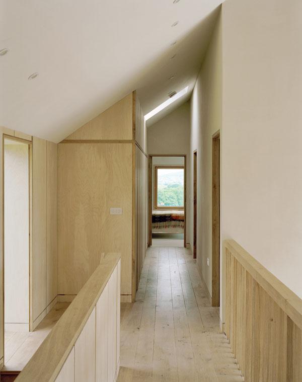 Jednoduchý interiér se strohými liniemi je sjednocen březovou překližkou. Dřevo je ostatně hlavním motivem celého interiéru. Majitelé zkrátka ctí přírodu. Foto Feilden Fowles