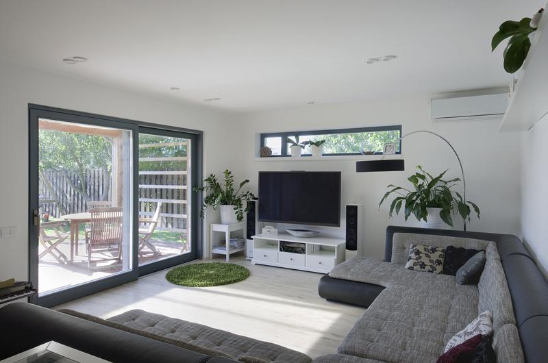 Obývací pokoj, laděný do odstínů šedé, je zcela v duchu aktuálních trendů propojen s exteriérem – nejen díky velkoformátovým oknům, ale i přímým napojením na krytou terasu.