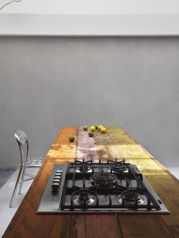 Plynovou varnou desku umístil majitel a architekt v jedné osobě na starý, zubem času poznamenaný stůl z prken jakoby kdysi natřených zářivými barvami. Skvěle kontrastují s cementovým povrchem stěn a hliníkovou židlí. Foto: Denilson Machado – MCA Estúdio