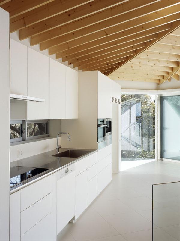 """Ze stejného důvodu úložné prostory, kuchyňská linka a další nezbytný nábytek stojí """"cudně"""" v koutě, resp. jsou rozmístěny podél zdí. Foto: Masao Nishikawa"""