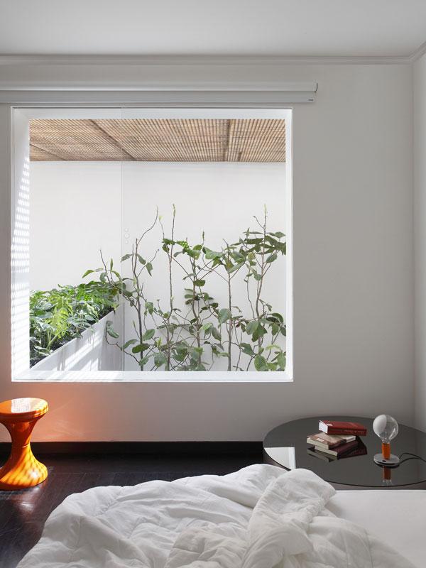 Obrovské okno v ložnici umožňuje neustálý kontakt spáče s venkovním prostředím. Uklidňující pohled do zeleně je chráněn před ostrými slunečními paprsky perforovanými dřevěnými deskami – muxarabie. Foto: Denilson Machado – MCA Estúdio