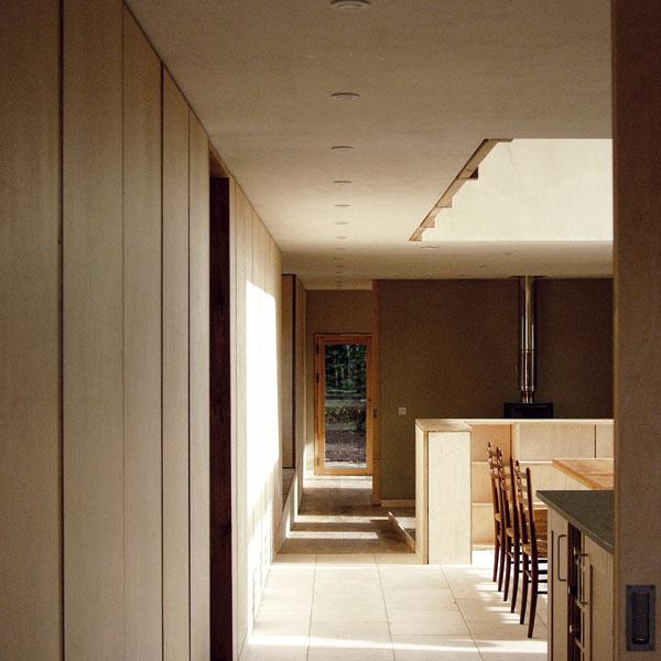 Stejně jako vprvním patře, i vpřízemí prochází celým interiérem páteřní chodba a tvoří tak základní komunikační osu domu. Na konci odmění procházejícího pohledem do uklidňující zeleně. Foto Feilden Fowles