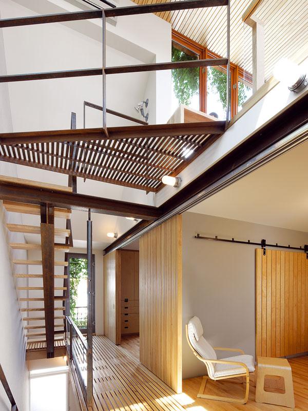 Optické triky hrály při přestavbě velkou roli. Dům je i díky dřevěným podlahovým roštům, které propouštějí světlo až do přízemí, mnohem vzdušnější a světlejší. Jen co děti trochu odrostou, chystá se Paul mezery mezi prkny ještě zvětšit. Foto Marc Cramer