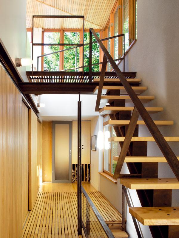 Rodina si pochvaluje otevřený vnitřní prostor, který jim umožňuje snadnou komunikaci napříč celým domem. Odstranění starého schodiště a jeho nahrazení lehkou ocelovou konstrukcí s dřevěnými schodnicemi vykouzlily zbudovy domov dostatečně prostorný pro čtyřčlennou rodinu. Foto Marc Cramer