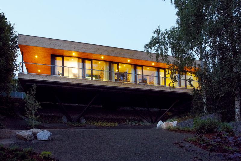 Když na pozemek padne šero, může pozorovatel nabýt dojmu, že dům se vznáší ve vzduchu. Důmyslné konstrukční řešení základů je díky tmavé barvě téměř neviditelné. Foto Vítezslav Hájek