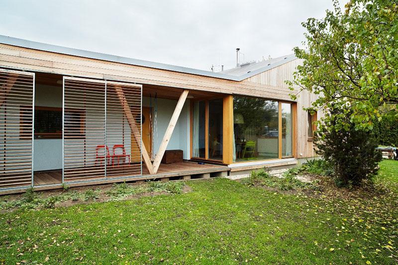 Do domu se vstupuje z venkovní dřevěné terasy, která zároveň vytváří kryté zápraží. Odvětranou fasádu tvoří modřínová prkna na roštu. Foto: Petr Karšulín
