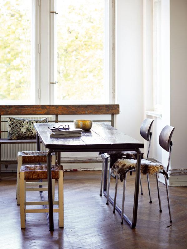 Jídelní stůl v obýváku je originál – prototyp z dílny bratrů Haussmannů. Vyplétané židle bez opěradla ještě pamatují NDR a lavici našli domácí na odlehlé silnici mezi vesnicemi. Foto Sabrina Rothe