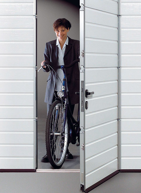 Sekční garážová vrata s integrovanými dveřmi bez vysokého prahu. Tak se snadno dostanete kjízdnímu kolu nebo zahradnímu nářadí, aniž byste museli otvírat celá vrata. foto: Hörmann