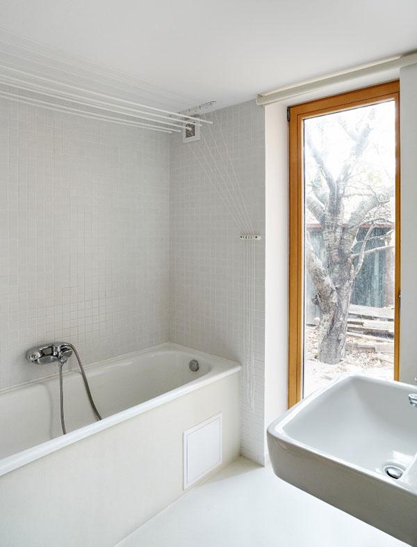 Z koupelny v přízemí je velkorysý výhled do zahrady. Stejně jako v celém interiéru zde dominuje bílá. Foto: Petr Karšulín