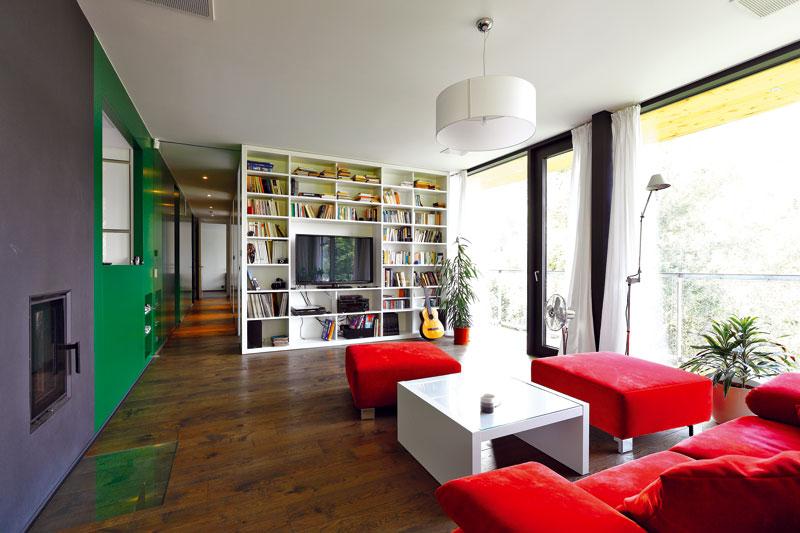 Interiér je zařízen relativně skromně. Dominují mu neutrální tóny, výraznějším barevným akcentem je jen zelená stěna jako téma, které se táhne skoro celým domem, ačervená sedací souprava vobývacím pokoji. Foto Dano Veselský