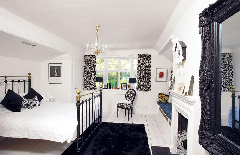 Rokoková ložnice je zařízená různými černými a bílými kusy nábytku. Doplňky včetně bílých kukačkových hodin nad krbem ctí týž styl i barevnost. FOTO Carlos Dominguez