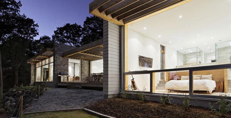 Pokud přicházíte k domu ze severu, otevře se vám pohled na fasádu s přírodně ošetřeného dřeva. Jižní strana domu naopak umožňuje kochat se okolní přírodou díky velkoryse proskleným plochám. Foto: Terence Tourangeau