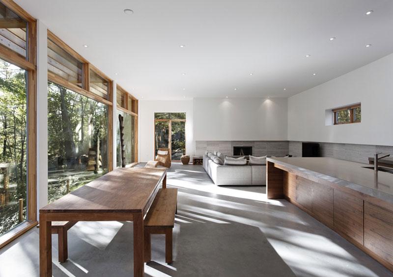 Slunce pronikající do domu skrze bariéru stromů vytváří v obývací části hru světel a stínů, která se tak stává ústředním motivem v čistém, minimalisticky pojatém interiéru. Foto: Terence Tourangeau