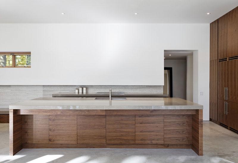 Monolit kuchyňského ostrova vzdává hold přírodním materiálům. Dřevo a kámen jsou nejtypičtější prvky této lesní rezidence – najdete je jak v interiéru, tak v exteriéru. Foto: Terence Tourangeau