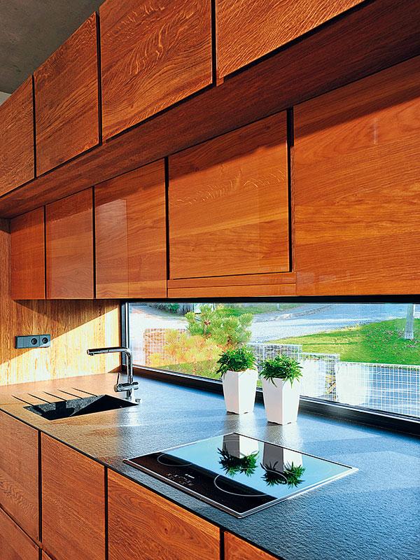 Kuchyňská linka vyniká nejen celkovým řešením, ale istrukturou materiálu. Dub drásaný se na ní střídá sdubem vysokého lesku. Pracovní plocha je zafrické žuly. FOTO Schüco CZ