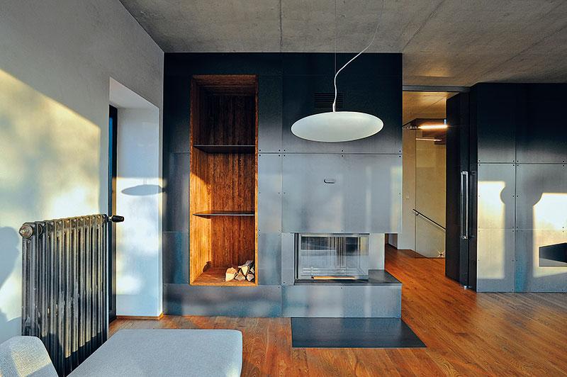 Stěna vobýváku, která byla záměrně obložena plechem, krásně kontrastujícím sdřevěnými podlahami anábytkem. FOTO Schüco CZ